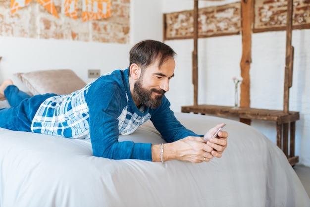 Man zit ontspannen in bed thuis op de mobiele telefoon