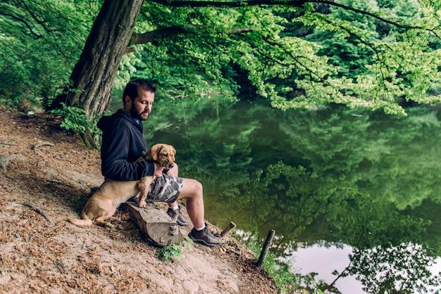 Man zit op de bank met de hond aan het meer