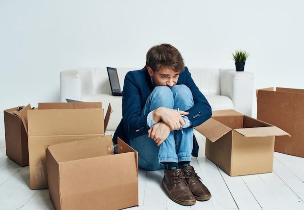 Man zit op de grond met kartonnen dozen met bewegende dingen