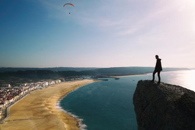 Man zit op de klif op zoek van bovenaf op zee strand en kleine stad