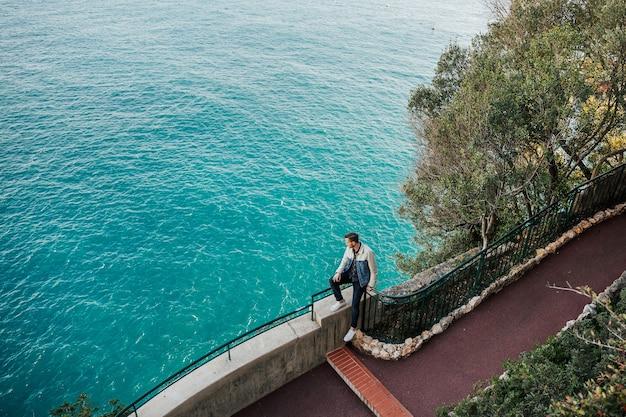 Man zit op de steen in de buurt van zee met azuurblauw water op een zonnige dag in de winter