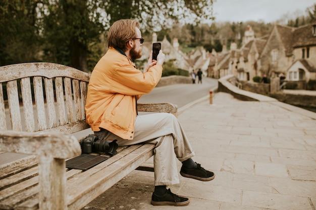 Man zit op een bankje en maakt foto's op zijn telefoon in het dorp