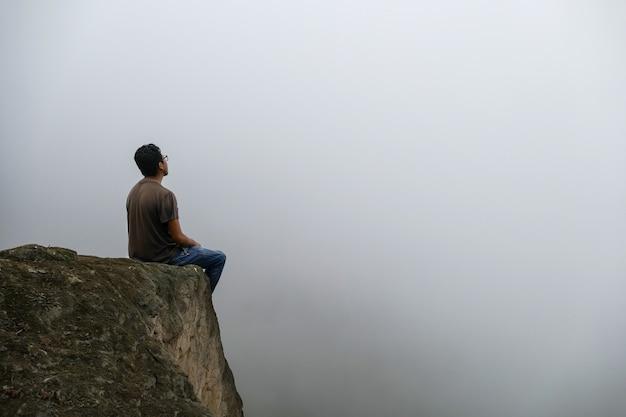 Man zit op een klif in een vallei en kijkt naar de mist