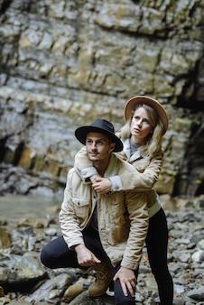 Man zit op een rots, kijkt in de camera, achter hem glimlacht een vrouw tegen de achtergrond van de heuvels. liefdevol paar knuffels op de a berg in de altai
