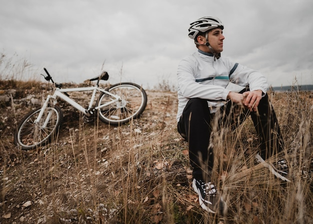 Man zit op het gras naast zijn mountainbike