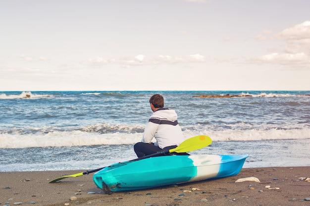 Man zit op kajak op zee strand