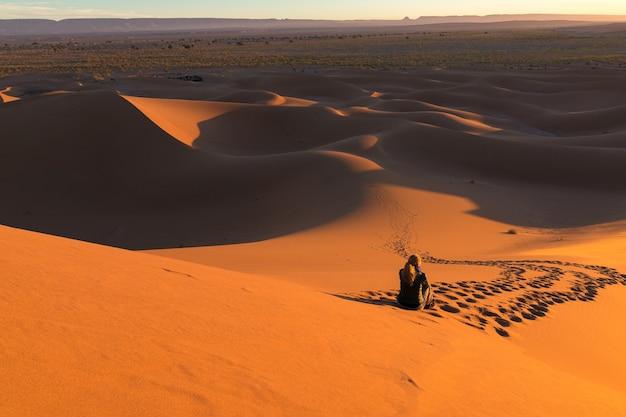 Man zit op zandduinen omringd door sporen in een woestijn