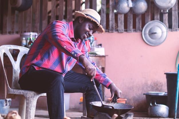 Man zitten en koken in de keuken