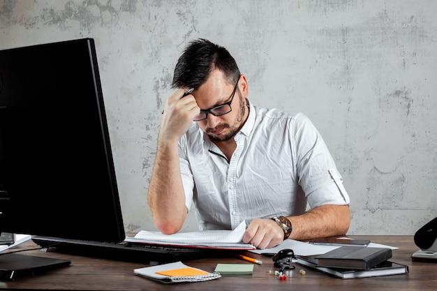 Man zittend aan een tafel op kantoor, bezig met belangrijke papieren.