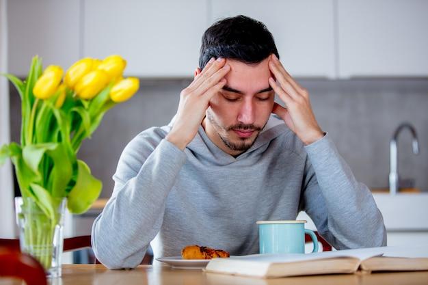 Man zittend aan tafel met een kopje koffie of thee en een boek.