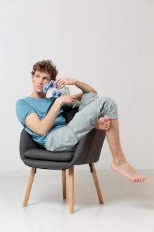 Man zittend in een stoel en bloemen te houden