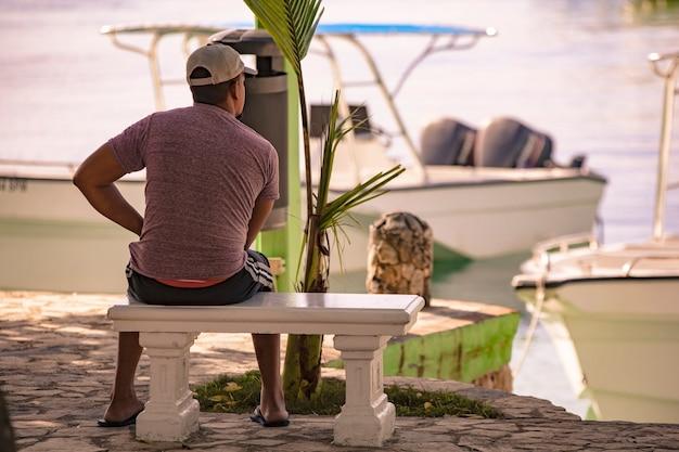 Man zittend op de bank kijkt naar de zee vanuit de haven van bayahibe in de dominicaanse republiek