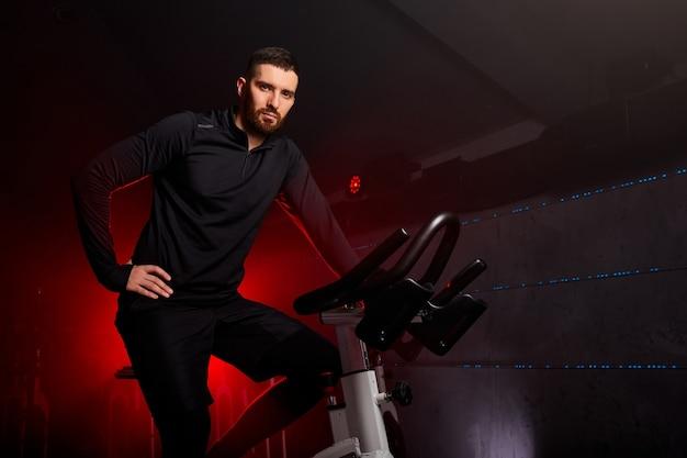 Man zittend op de fiets in de sportschool poseren op camera, training fietsen in de sportschool, met de bedoeling van de gezondheidszorg. rode neon rokerige ruimte op de achtergrond