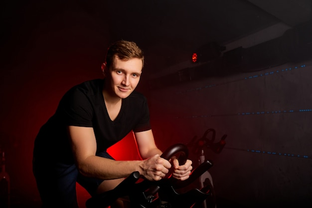 Man zittend op de fiets in de sportschool poseren op camera, training fietsen in de sportschool, met de bedoeling van de gezondheidszorg