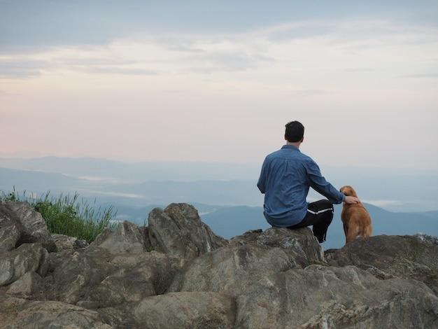 Man zittend op de rots en een hond aaien, omringd door bergen onder een bewolkte hemel