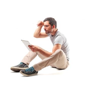 Man zittend op de vloer en het gebruik van een tablet