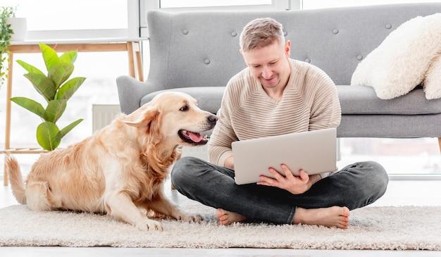 Man zittend op de vloer en kijken naar laptop met golden retriever hond thuis