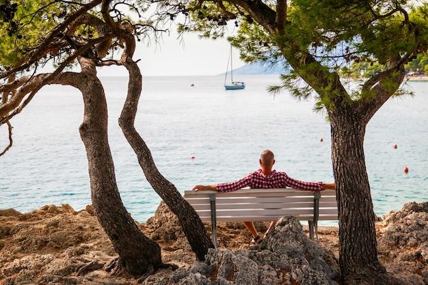 Man zittend op een bankje aan de oever van een klein dorpje brela, makarska riviera, kroatië