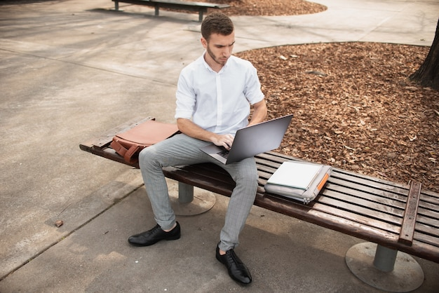 Man zittend op een bankje en die op laptop werkt