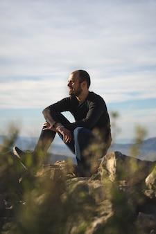 Man zittend op een rots achter een struik, kijkend naar de zon op de berg, jonge blanke man. het dragen van jeans met een zwart t-shirt. blauwe lucht licht bewolkt.