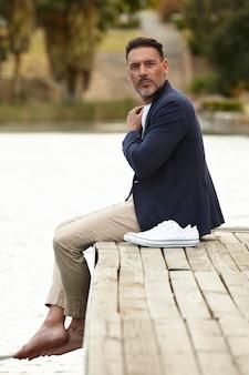 Man zittend op een steiger poseren