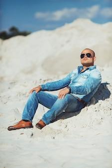 Man zittend op het zand, een gebruinde jeans kleding