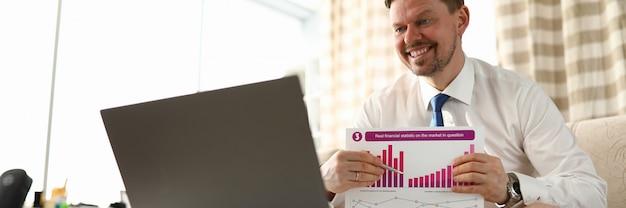 Man zonder broek toont rapport voor laptop