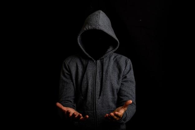 Man zonder gezicht in een kap houdt iets in zijn handen op een donkere achtergrond.