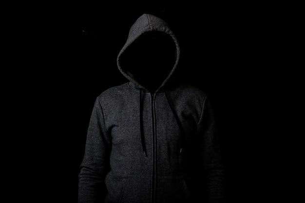 Man zonder gezicht in een kap op een donkere achtergrond.