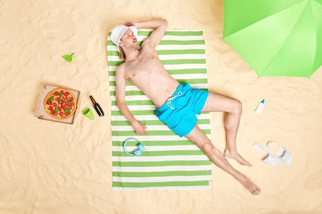 Man zonnebaadt alleen en doet een dutje op zandstrand draagt witte panama shorts ligt op groen gestreepte handdoeksteunen aan zee