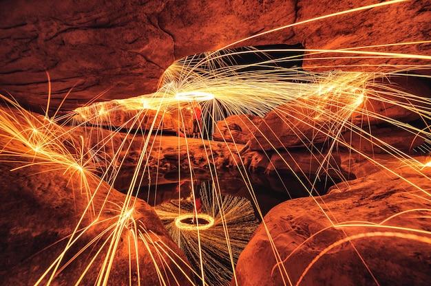 Man zwaaiende vonkenvuurwerveling in grot met stenen gaten en vijverreflectie in de nacht bij sam phan bok