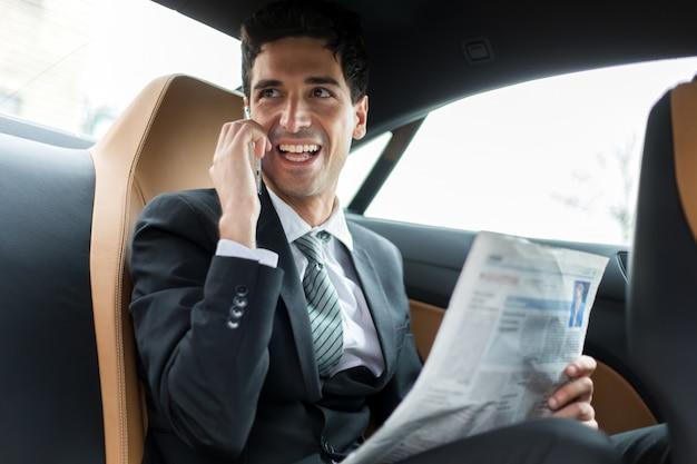 Manager aan de telefoon zit op de achterbank van een auto
