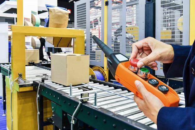 Manager check en control automatisering kartonnen dozen op transportband in distributiemagazijn.