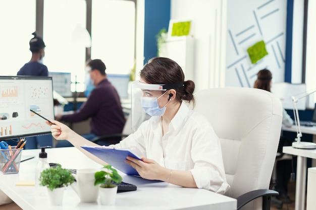 Manager die bescherming draagt tegen covid 19 tijdens wereldwijde pandemie. werknemers met vizieren die in de werkruimte van een bedrijf werken, met respect voor de sociale afstand die gegevens en grafieken analyseert.