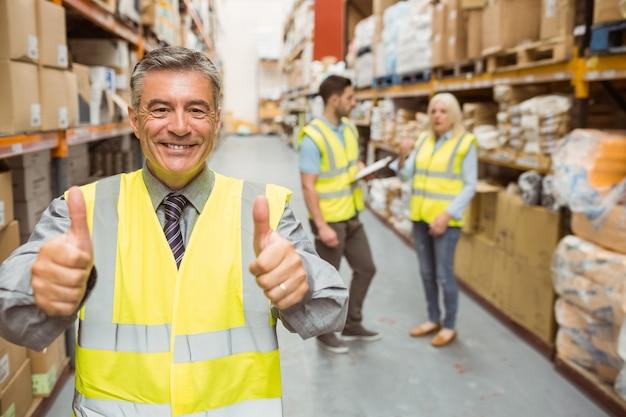 Manager die bij camera glimlachen die duimen toont