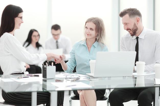 Manager die de hand schudt met de klant tijdens een kantoorvergadering. concept van samenwerking