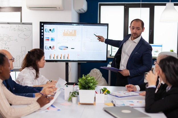 Manager die een briefingpresentatie houdt in het monitorproject van de conferentieruimte. bedrijfspersoneel bespreekt nieuwe zakelijke toepassing met collega's die naar het scherm kijken