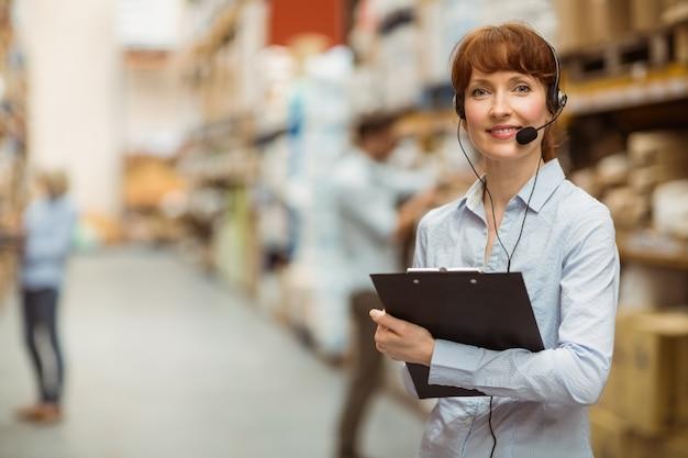 Manager die een hoofdtelefoon draagt terwijl klembord