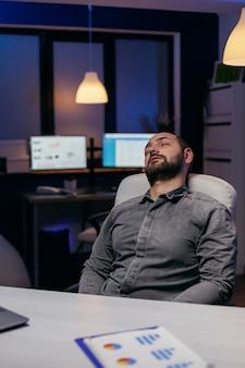 Manager die een pauze neemt om uit te rusten tijdens het werken aan projectdeadling. workaholic-medewerker die in slaap valt omdat hij 's avonds laat alleen op kantoor werkt voor een belangrijk bedrijfsproject.