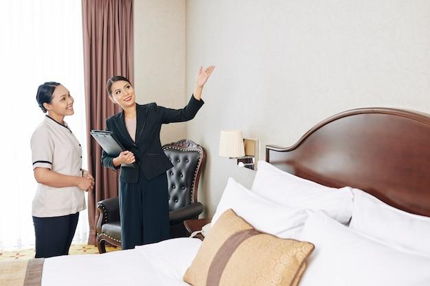 Manager die hotelkamer onderzoekt