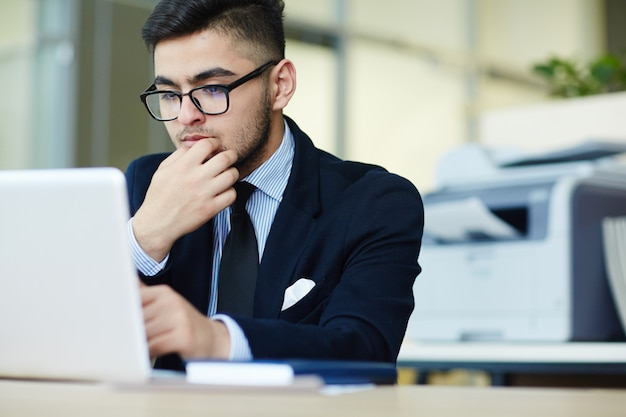 Manager die met laptop op kantoor werkt