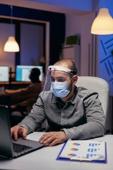Manager en collega's doen overuren met vizier tegen covid-19. gestresste man in bedrijf die hard werkt om een project af te werken met een gezichtsmasker als veiligheidsmaatregel vanwege de pandemie van het coronavirus.