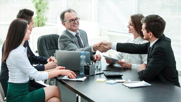 Manager en klant schudden elkaar de hand na bespreking van het contract.foto met plaats voor tekst