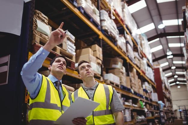 Manager en werknemer praten in magazijn