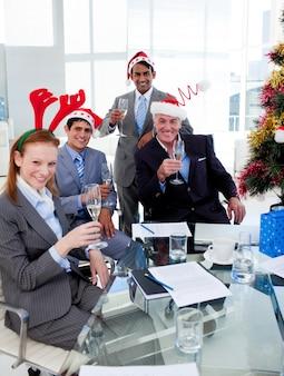 Manager en zijn team roosteren met champagne tijdens een kerstfeest