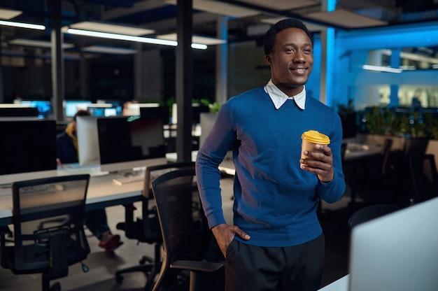 Manager houdt kopje koffie, kantoorlevensstijl. mannelijke persoon op laptop, moderne werkplek