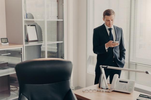 Manager in bedrijfskleding bladert webpagina's en chats online met smartphone