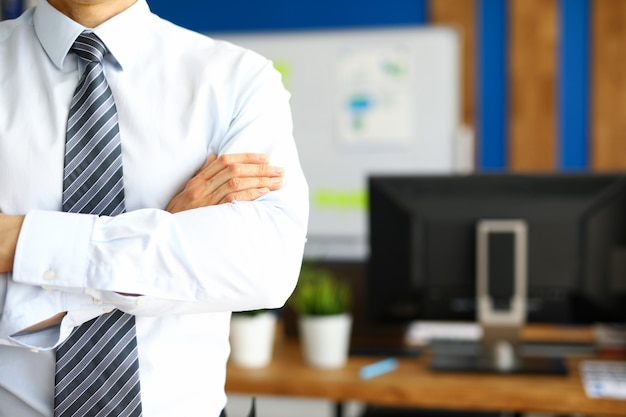 Manager in een stropdas staat op kantoor met zijn armen over elkaar. man in zakelijke kleding op de achtergrond van kantoormeubilair