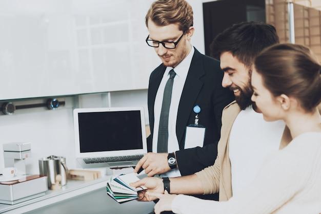 Manager in pak met laptop toont kleurstalen.