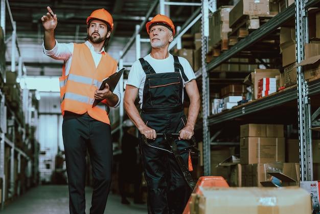 Manager in veiligheidshelm praten met magazijnmedewerker